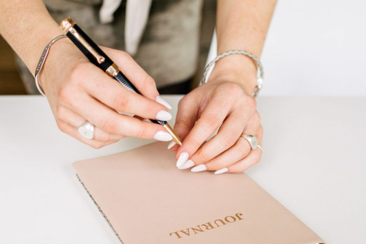 A woman writing on a brown journal